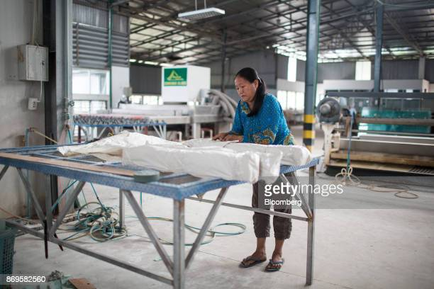 A worker wraps sheets of glass for transport in the packaging department at the Somvang Glass Factory on the outskirts of Vientiane Laos on Wednesday...