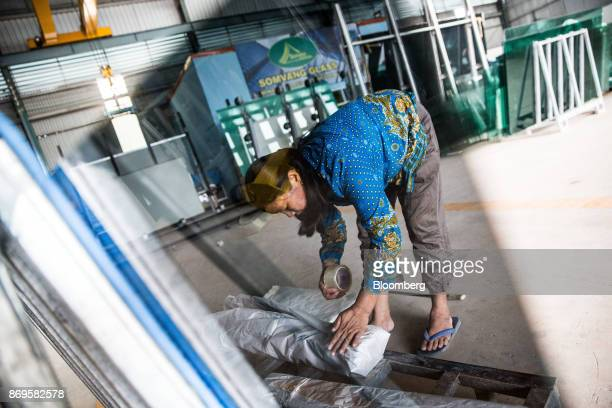 A worker wraps sheets of glass in the packaging department at the Somvang Glass Factory on the outskirts of Vientiane Laos on Wednesday Nov 1 2017...
