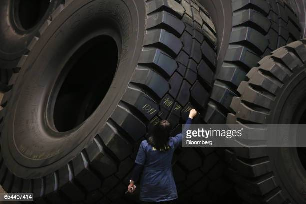 A worker writes numbers on the tread of a large 4000R57 sized tire after inspecting it in the control room at the Belshina JSC tire factory in...
