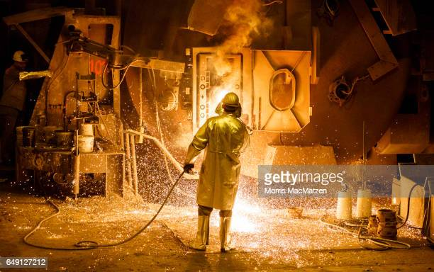 A workercleans a big melting pot at the Salzgitter AG steelworks on March 7 2017 in Salzgitter Germany Salzgitter is among Europe's biggest steel...