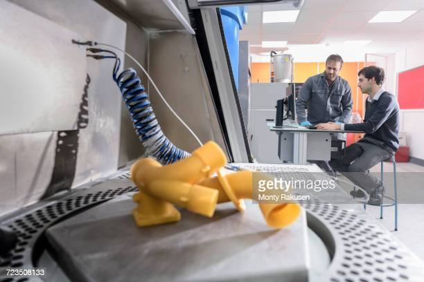 Workers 3D printing components in precision casting factory