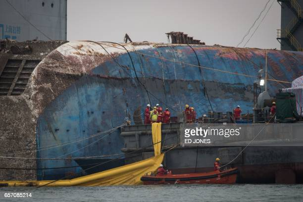 TOPSHOT Workers aboard a Chinese salvage vessel participate in the salvage operation of the Sewol ferry off the coast of South Korea's southern...