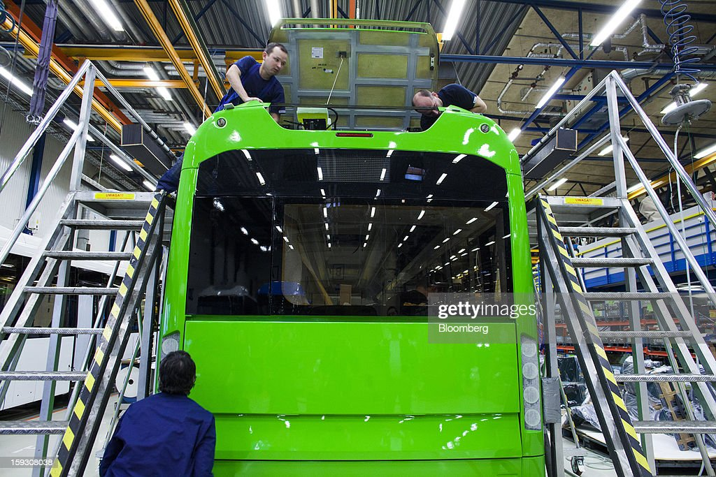 Workers access the rear roof section of a bus during assembly at Volvo AB's manufacturing plant in Wroclaw, Poland, on Friday, Jan. 11, 2013. Volvo plans to end bus making in Saeffle by June 2013, and will consolidate the business in Europe to its main plant in Wroclaw, Poland, the Gothenburg, Sweden-based company said. Photographer: Bartek Sadowski/Bloomberg via Getty Images