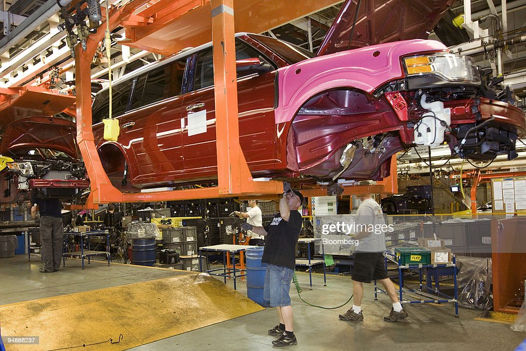 Workers add parts to a new Ford Flex as it makes its way down the assembly line at the Ford Motor Co Oakville factory in Oakville Ontario Canada on...