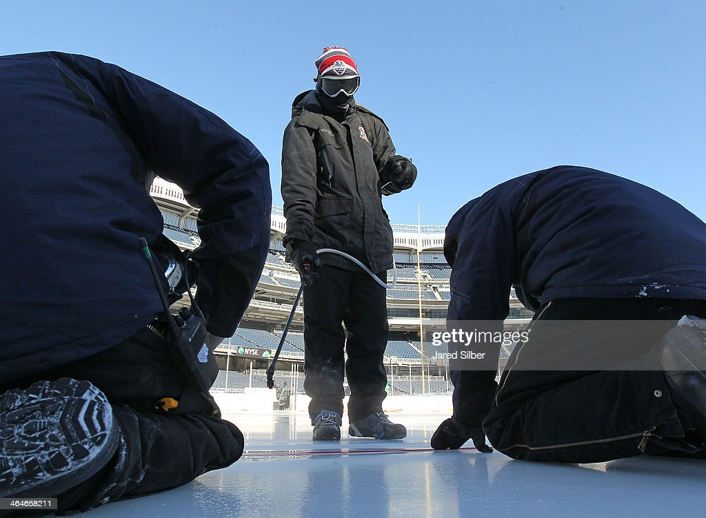 Workers add the lines and logos during the rink build for the 2014 Coors Light Stadium Series Games at Yankee Stadium on January 23, 2014 in the Bronx borough of New York City. The games are scheduled to be played on Sunday, January 26, 2014 and Wednesday, January 29, 2014.