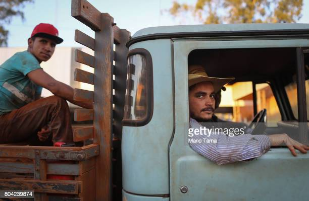 Workers Ademir and Felippe sit in a truck at a cattle feed lot in the Amazon on June 28 2017 near Chupinguaia Rondonia state Brazil The confinement...
