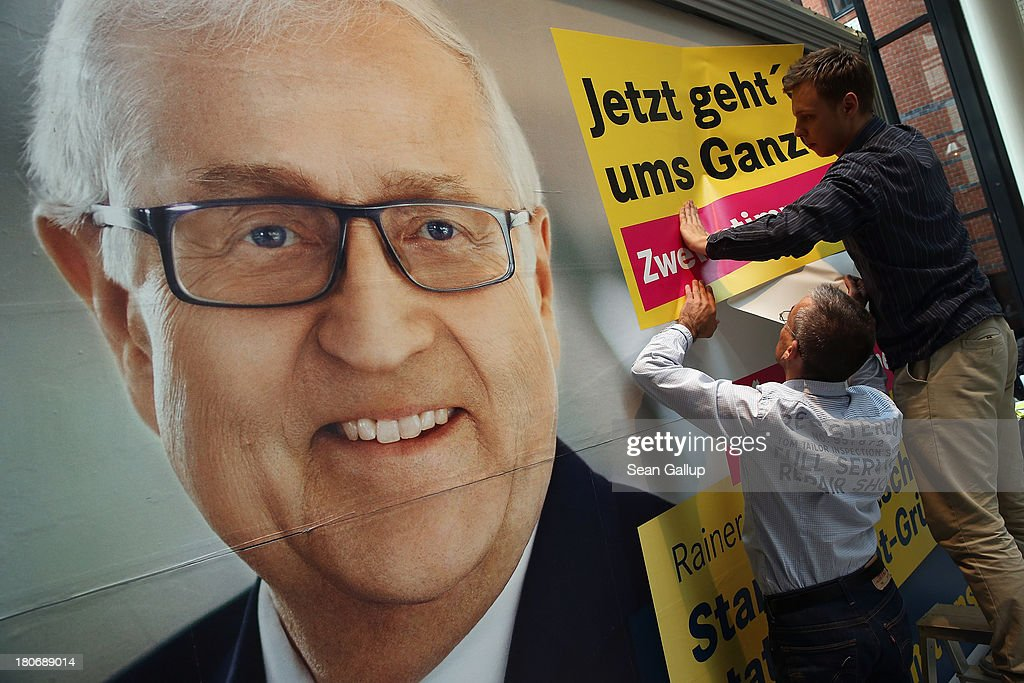 'Now it's about the whole thing' onto an election campaign billboard that depicts lead candidiate of the German Free Democrats (FDP) Rainer Bruederle at FDP party headquarters on September 16, 2013 in Berlin, Germany. The FDP faired disastrously in Bavarian state elections held the previous day and failed to get enough votes to retain seats in the Bavarian parliament. Germany faces federal elections on September 22 and the FDP, which is the current German government coalition partner with the German Christian Democrats (CDU), is facing an uphill battle.