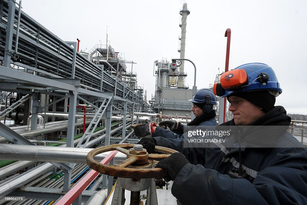 Workers adjust a supply at the Mozyr oil refinery some 300 km south of Minsk in Mozyr on January 4, 2013.