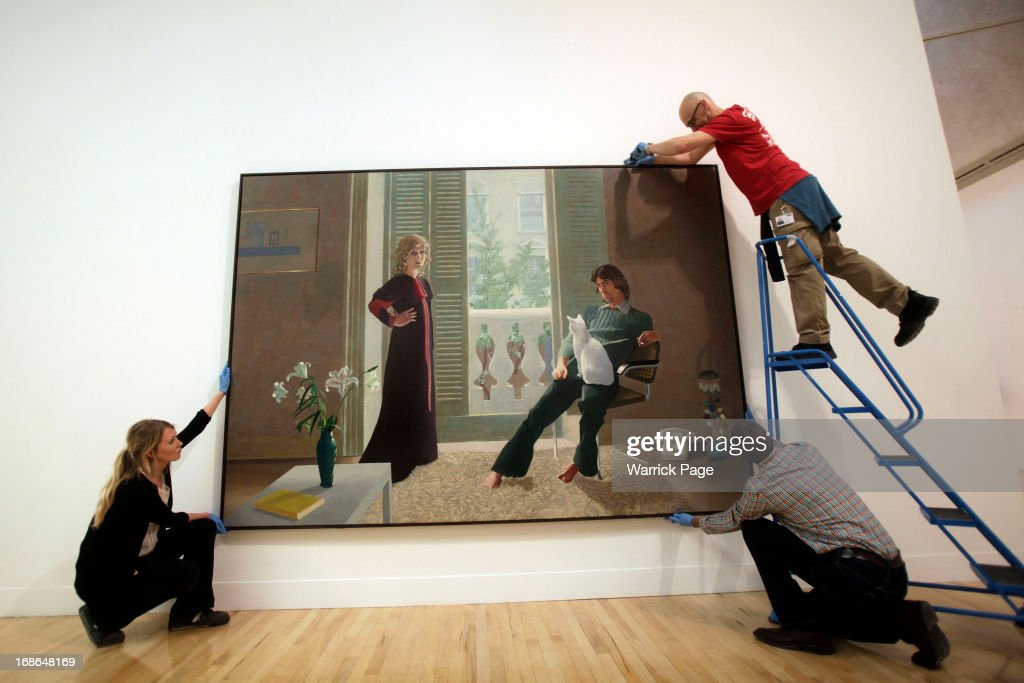 Workers adjust David Hockney's Mr and Mrs Clark and Percy for display at the Walk through British Art exhibition at Tate Britain on May 13, 2013 in London, England. Visitors will experience a completely new presentation of the world's greatest collection of British art, the national collection of British art will be displayed in a continuous and purely chronological display from the 1500s to the present day.