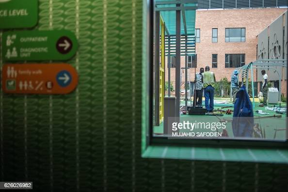 Workers and builders work on an outside yard at the Nelson Mandela Children's hospital on November 14 in Johannesburg that will be inaugurated on...