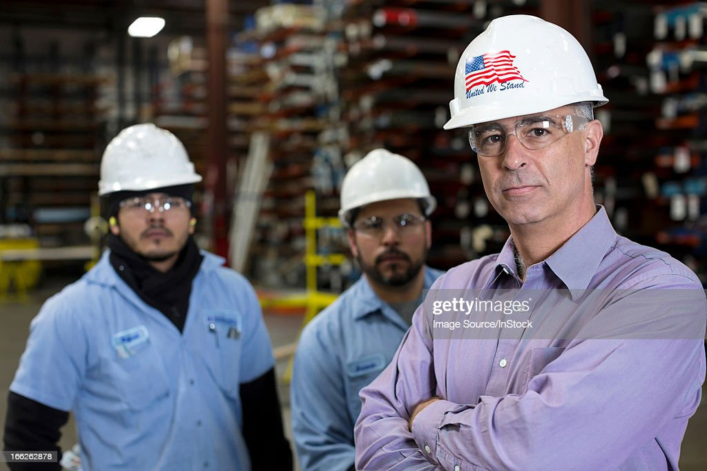 Workers and businessman in metal plant : Stock Photo