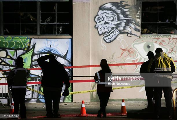 Workers and emergency responders look at a warehouse in which a fire claimed the lives of at least thirtysix people on December 5 2016 in Oakland...