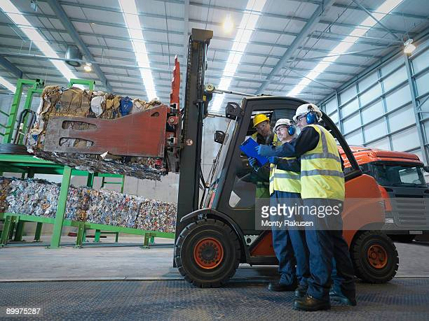 Workers And Forklift Truck In Plant