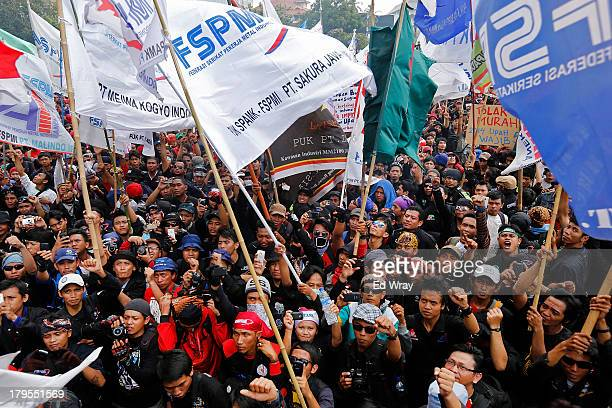 Workers and labor activists protest against a proposed cap on wage increases outside the Presidential Palace on September 5 2013 in Jakarta Indonesia...