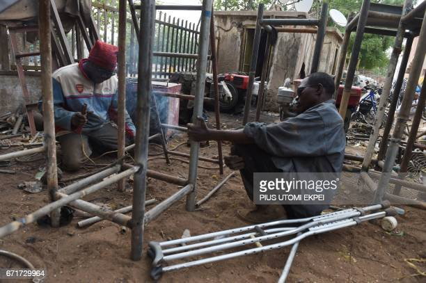 Workers and members of the Polio Victims Trust Association tries to weld a panel at the workshop in Kano northwest Nigeria on April 21 2017 The World...