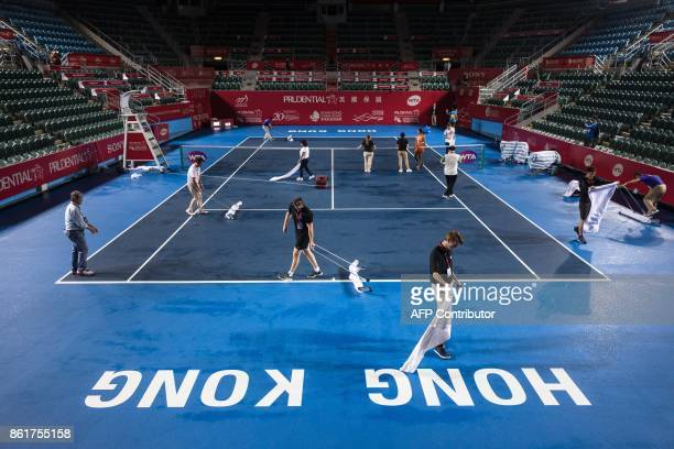 TOPSHOT Workers and officials dry the court after heavy from Typhoon Khanun which delayed the start of the women's singles final between Russia's...