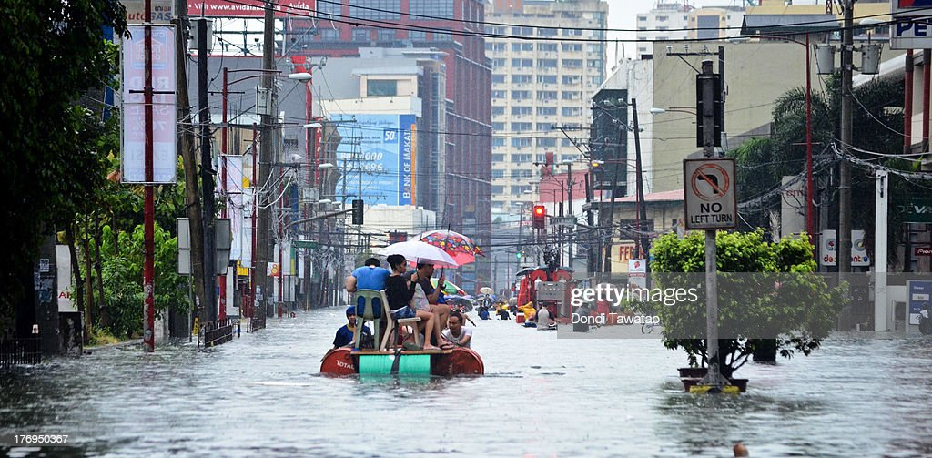 Workers and pedestrians ride pedicabs and makeshift rafts on a flooded street that submerged parts of the financial district of Makati on August 20, 2013 in Makati City south of Manila, Philippines. Schools, government offices and financial markets suspended classes and work except for rescues and disaster response as torrential rains enhanced by the southwestern monsoon inundated much of the metropolis for a second day. Major roads were impassable as floodwaters reached waist or neck deep in some areas forcing thousands of residents living near waterways and creeks to evacuate their homes and seek shelter. At least seven fatalities were recorded with thousands more still needing to be rescued.
