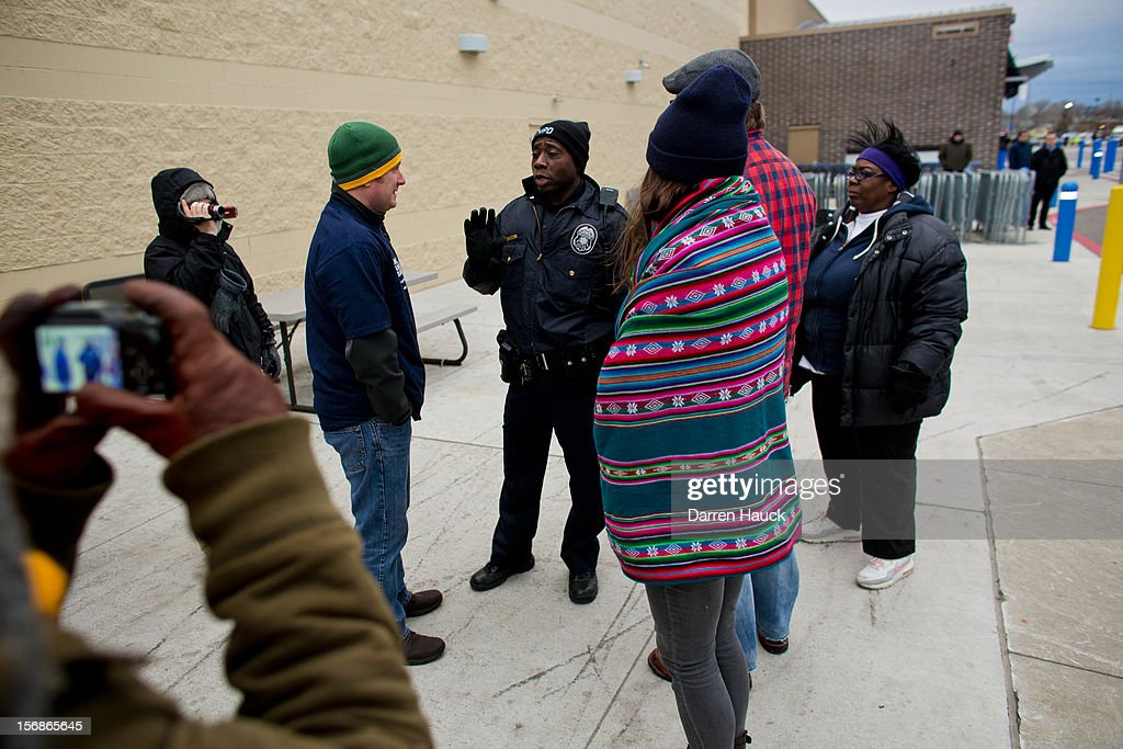 Workers and supporters are greeted by a Milwaukee Police officer as they march outside of a local Wal-Mart retail store on Black Friday November 23, 2012 in Milwaukee, Wisconsin. The protestors were calling for better wages and working conditions for the employees.