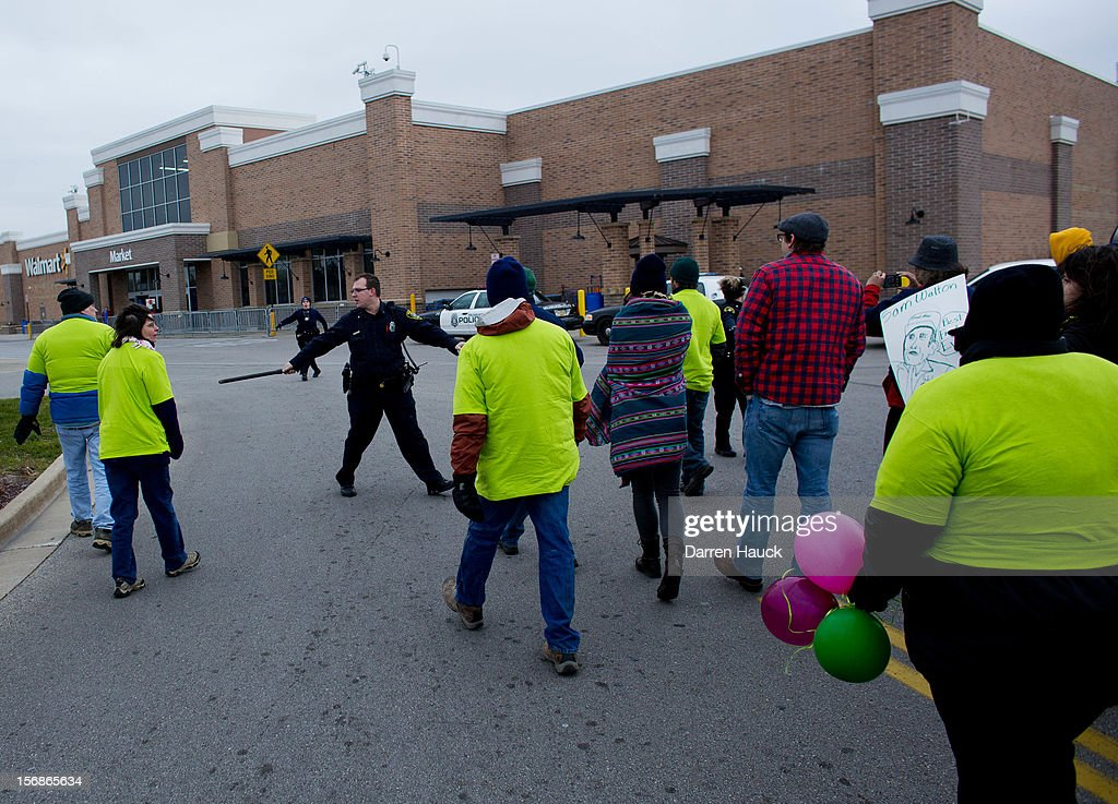 Workers and supporters are greeted by Milwaukee Police officers as they march outside of a local Wal-Mart retail store on Black Friday November 23, 2012 in Milwaukee, Wisconsin. The protestors were calling for better wages and working conditions for the employees.