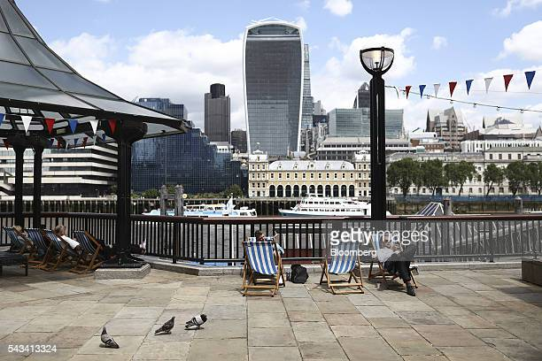 Workers and tourists rest in deckchairs as 20 Fenchurch Street also known as the 'WalkieTalkie' center stands beyond in London UK on Tuesday June 28...