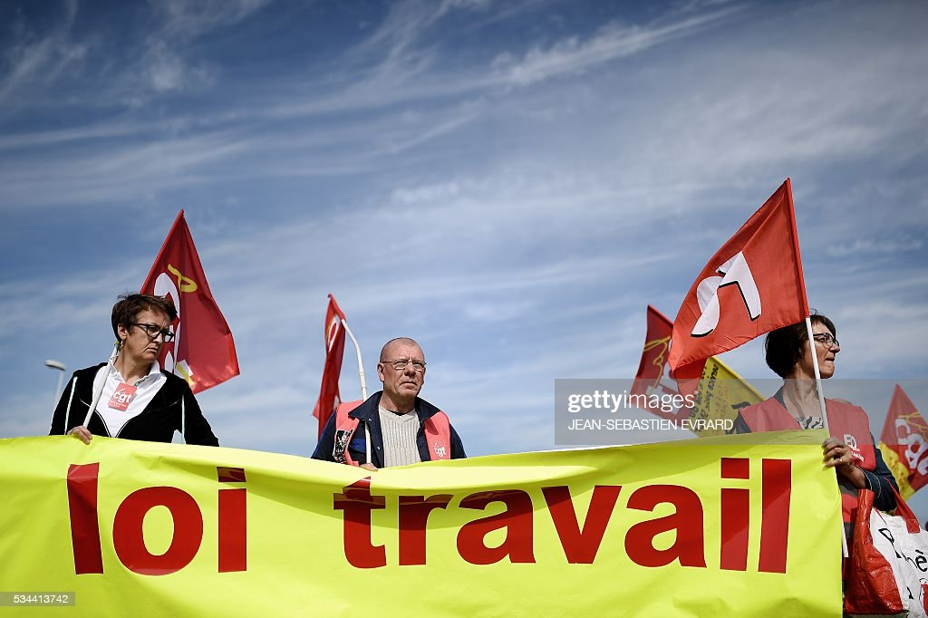 Workers and union members hold a banner that reads, 'Work law' as they rally in Saint-Nazaire, western France, to demonstrate against the government's planned labour law reforms on May 26, 2016. France's Socialist government has bypassed parliament and rammed through a labour reform bill that has sparked two months of massive street protests. EVRARD