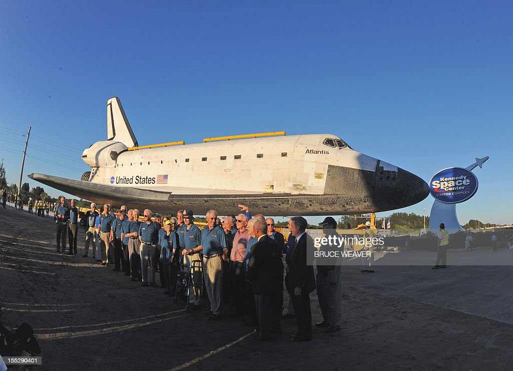 Workers and visitors watch as the US Space Shuttle Atlantis moves on November 2, 2012 to the Visitors Center at Kennedy Space Center in Cape Canaveral, Florida, for permanent display. The spacecraft traveled 125,935,769 miles (202,673,974 kms) during 33 spaceflights, including 12 missions to the International Space Station. Its final mission, STS-135, closed out the Space Shuttle Program era with a landing on July 21, 2011. AFP PHOTO/Bruce Weaver