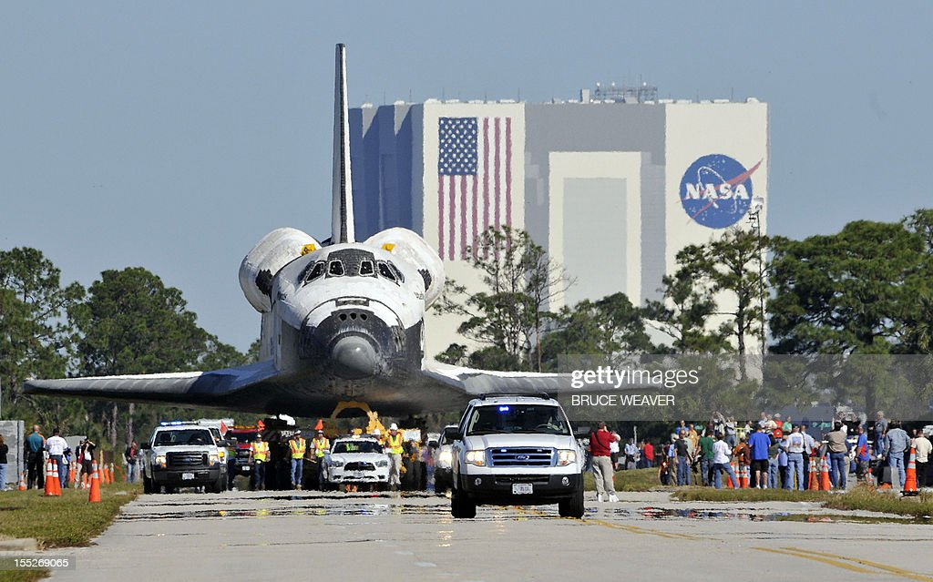 Workers and visitors watch the US Space Shuttle Atlantis moves on November 2, 2012 to the Visitors Center at Kennedy Space Center in Cape Canaveral, Florida, for permanent display. The spacecraft traveled 125,935,769 miles(202,673,974kms) during 33 spaceflights, including 12 missions to the International Space Station. Its final mission, STS-135, closed out the Space Shuttle Program era with a landing on July 21, 2011. AFP PHOTO/Bruce Weaver