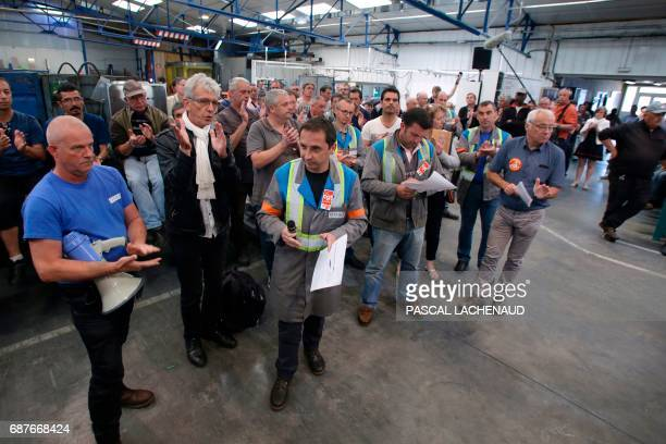 Workers applaud as CGT union representatives Patrick Brun Vincent Labrousse and Yann Augras and lawyer of workers JeanLouis Borie take part in a...