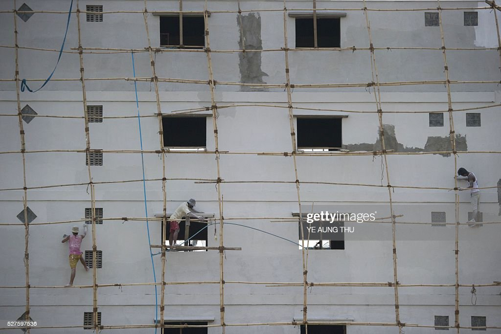 Workers apply paint to a building while standing on bamboo scaffolding at a construction site at Yangon on May 3, 2016. The resource-rich country now has one of the fastest growing economies in the world, and commercial hub Yangon has morphed from a crumbling relic to a rapidly transforming metropolis, with an ever-changing skyline. / AFP / YE