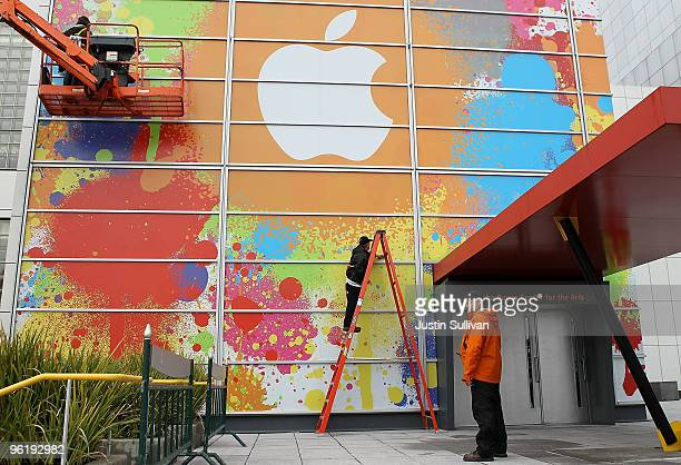 Workers apply the Apple logo to the exterior of the Yerba Buena Center for the Arts in preparation for an Apple special event January 26 2010 in San...