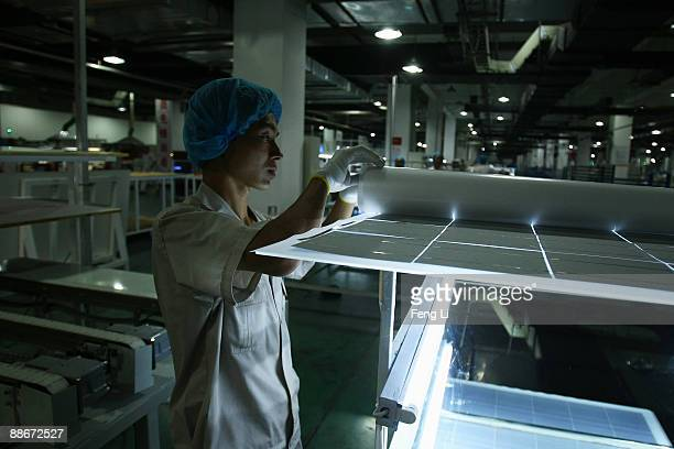 Workers are busy on the production line of photovoltaic board at the plant of Tianwei Yingli Green Energy Resources Co Ltd on June 24 2009 in Baoding...