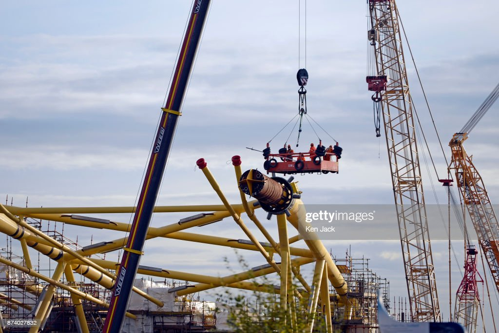 Workers are lowered on a platform amongst the giant steel structures for offshore wind power developments which dominate the Methil yard of engineering company BiFab, as the company faces the possibility of going into administration because of difficulties with a major contract, on November 14, 2017 in Methil, Scotland. Unions say staff have agreed to a 'work-in' - continuing to work to progress the orders in hand even though they may not be paid.