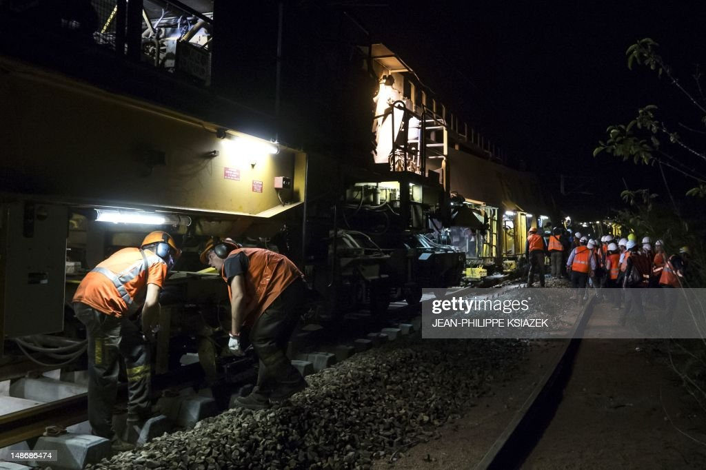 Workers are pictured on a working site at night on July 18, 2012 in Neuville-sur-Oise, northeast of Paris. The French railway company (SNCF) and the owner and manager of the French railway network company (RFF) launched a modernisation and renovation project on the suburban train of Paris' Regional Express Network (RER) line A to renew 70 km (43.5 miles) of tracks using a 'factory train' of 750 meters (2460 ft) long. AFP PHOTO / JEAN-PHILIPPE KSIAZEK