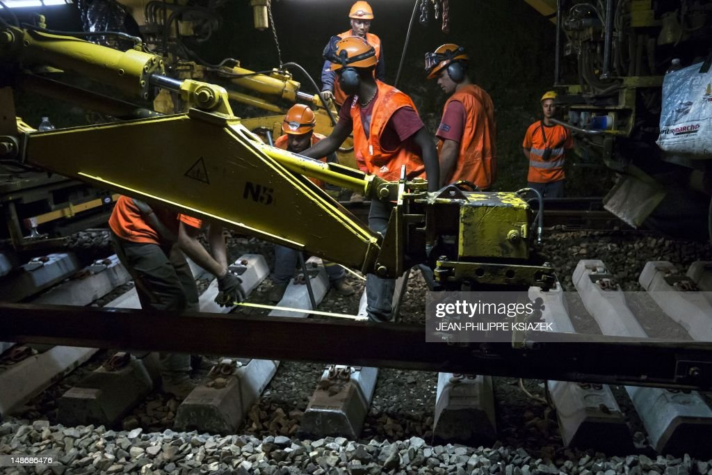 Workers are pictured on a working site at night on July 18, 2012 in Neuville-sur-Oise, northeast of Paris. The French railway company (SNCF) and the owner and manager of the French railway network company (RFF) launched a modernisation and renovation project on the suburban train of Paris' Regional Express Network (RER) line A to renew 70 km (43.5 miles) of tracks using a 'factory train' of 750 meters (2460 ft) long.