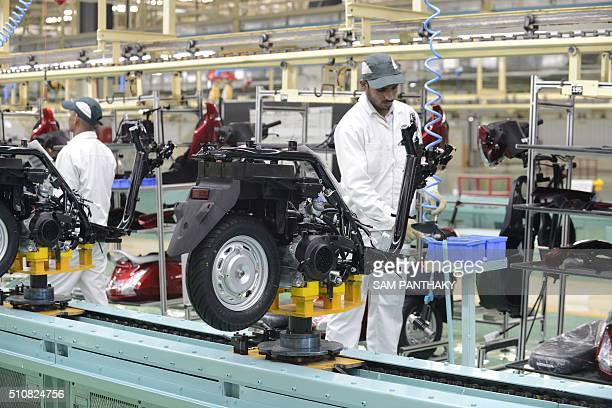 Workers are pictured on the assembly line of Activa scooters at the new plant of Honda Motorcycle and Scooter India Pvt Ltd in Vithalapur some 80 km...