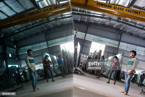 Workers are reflected in a sheet of glass at the Somvang Glass Factory on the outskirts of Vientiane Laos on Wednesday Nov 1 2017 Asia'ssmallest...