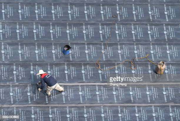 Workers are repairing the waterproof layer on the roof of an old apartment According to the data released by Chinese National Bureau of statistics on...
