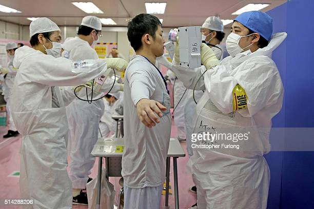 Workers are scanned for radiation exposure after returning from working outside at the Tokyo Electric Power Co's embattled Fukushima Daiichi nuclear...