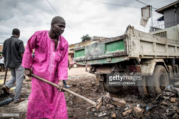 TOPSHOT Workers are see in Bitam in the north of Gabon near the border with Cameroon fixing the burned grounds of a warehouses on September 5 2016 On...