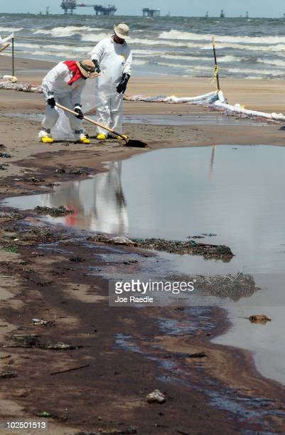 Workers are seen as they clear off some of the oil washing on to Fourchon Beach from the Deepwater Horizon oil spill in the Gulf of Mexico on June 28...