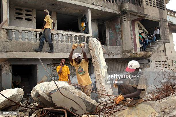 Workers are seen as they clear the rubble of a collapsed building on August 21 2010 in PortauPrince Haiti After the official list of presidential...