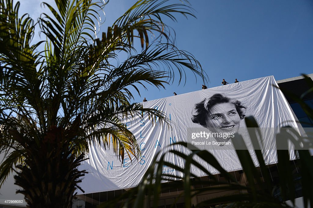 Workers are seen as they install the official poster of the 68th Cannes Film Festival on the facade of the Palais des Festivals on May 11 2015 in...