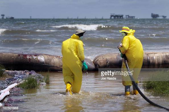 Workers are seen as they use a vacuum hose to capture some of the oil washing on to Fourchon Beach from the Deepwater Horizon oil spill in the Gulf...