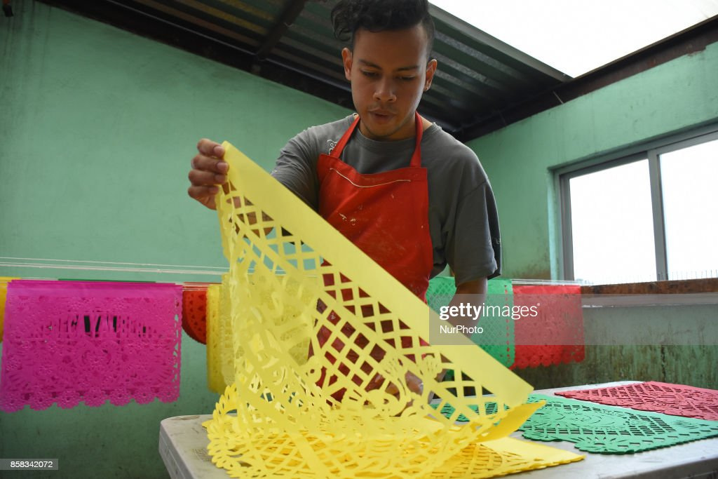 Workers are seen during the Manufactured of the traditional perforated paper to adorn the streets and offerings during the festivities of Mexican Tradition 'Day of the Dead' on October 06, 2017 in Mexico City, Mexico.