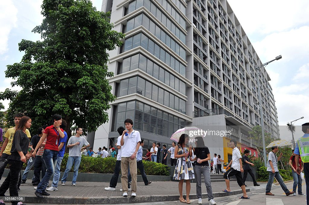Workers are seen next to a residential building at the giant Foxconn plant in Shenzen on May 26, 2010. The Taiwanese boss of Apple manufacturer Foxconn headed to a sprawling factory in southern China where a spate of worker suicides have stoked anger about labour conditions. Terry Gou, the chairman of Foxconn's parent company Hon Hai Precision, flew into the booming city of Shenzhen aboard his private jet with travelling Taiwanese reporters, urging the media to see the factory for themselves.