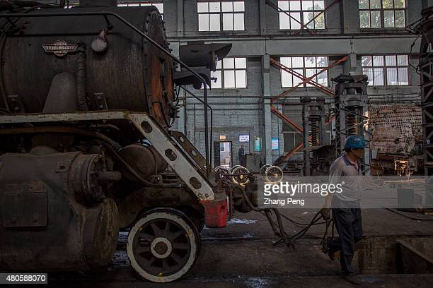 Workers are working in a maintenance factory for steam locomotives There are less and less steam trains to be repaired and the factory will be closed...