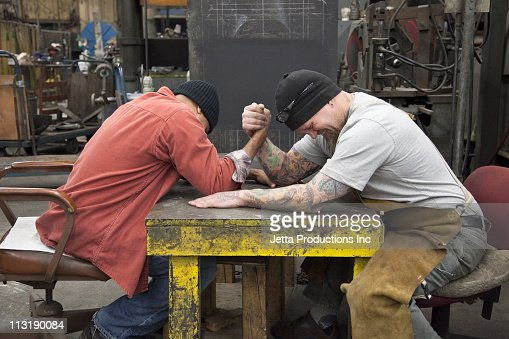 Workers arm wrestling in factory