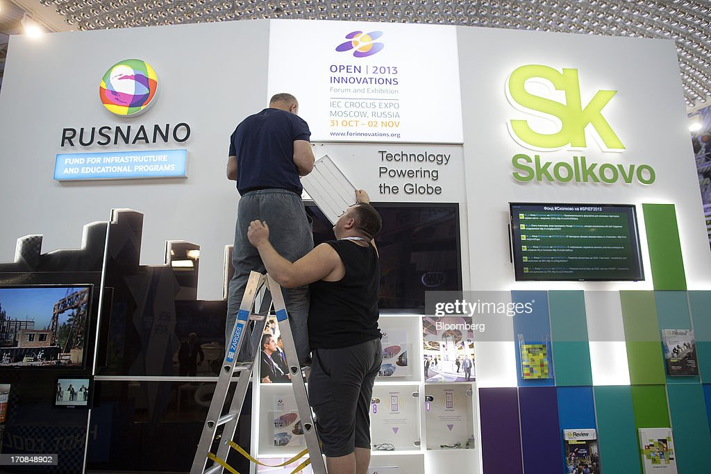 Workers arrange a display board at the OAO Rusnano and Skolkovo Foundation stands ahead of the St. Petersburg International Economic Forum 2013 (SPIEF) in St. Petersburg, Russia, on Wednesday, June 19, 2013. The Russian Deputy Prime Minister Igor Shuvalov told the conference that the country's World Trade Organization accession negotiations could be further delayed unless several remaining disputed matters are solved. Photographer: Simon Dawson/Bloomberg via Getty Images