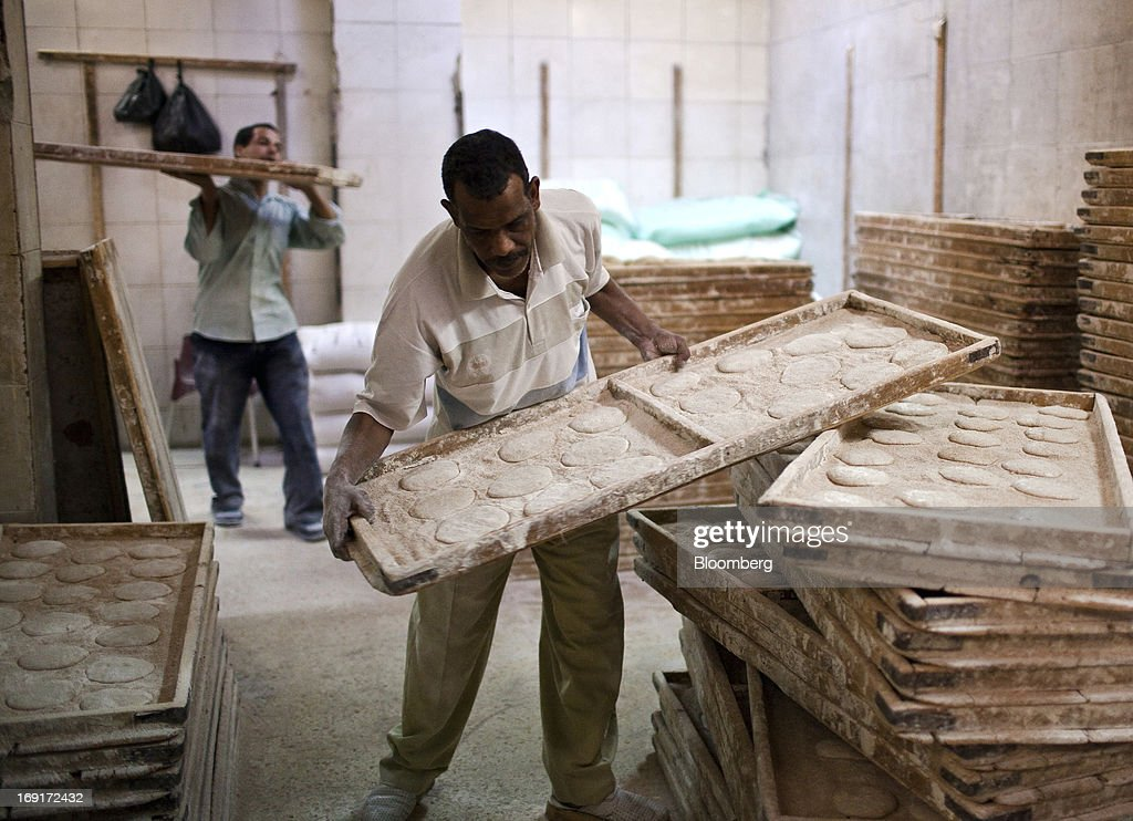 Workers arrange trays of dough for baking bread in a bakery in Cairo, Egypt, on Sunday, May 19, 2013. Egypt will curb wheat imports by 31 percent to 8 million metric tons in 2012-13, still enough to make it the world's biggest buyer, the U.S. Department of Agriculture estimates. Photographer: Shawn Baldwin/Bloomberg via Getty Images