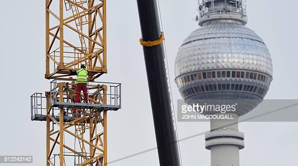 Workers assemble a crane at a construction site near Berlin's Alexanderplatz home of the landmark TV Tower on February 25 2016 / AFP / John MACDOUGALL